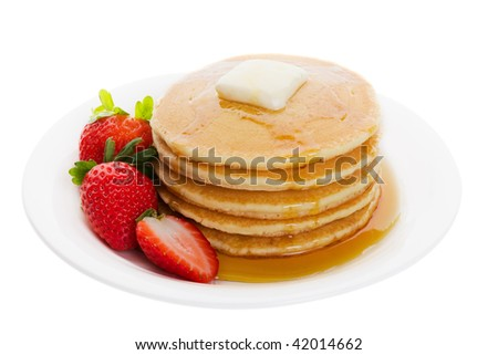Plate full of fluffy golden pancakes with strawberries and maple syrup