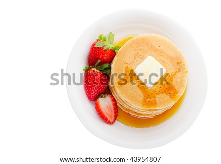 Plate full of fluffy golden pancakes with strawberries and maple syrup in overhead view