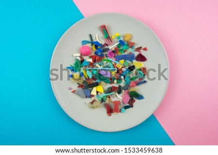 Plate full of microplastics. Plastic pollution concept.