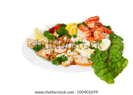 Plate full of orderves, edible flowers and shrimp isolated on a white background