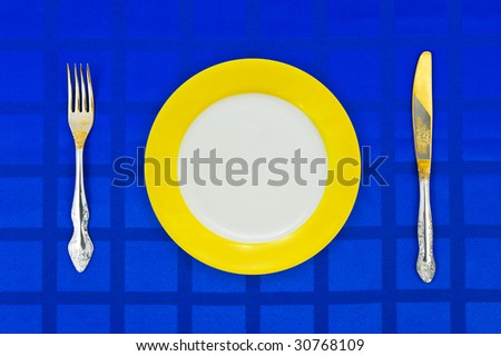 Plate, knife and fork on table cloth, food background