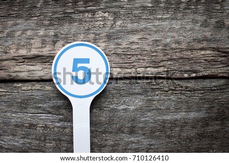 Plate number on a old wooden background. Numbers for lists or numbering concept.  #710126410