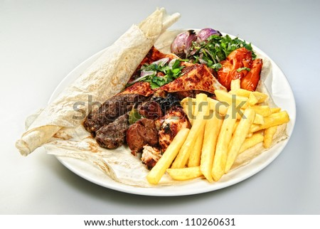 Plate of Arabic french fries with roasted meat and vegetables.