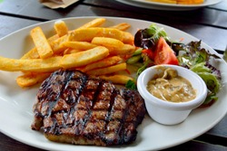 Plate of beef steak with salad, fried potatoes and mushroom sauce.