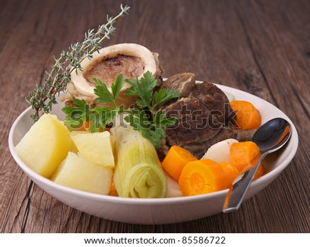 plate of beef stew on wooden background