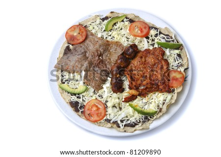 Plate of big tlayuda with beans, beef, sausage and chicken isolated on white background