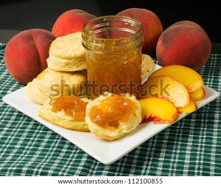 Plate of biscuits with peaches and peach jam or jelly