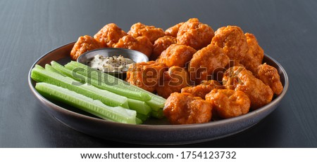 plate of boneless chicken wings with buffalo sauce and celery sticks