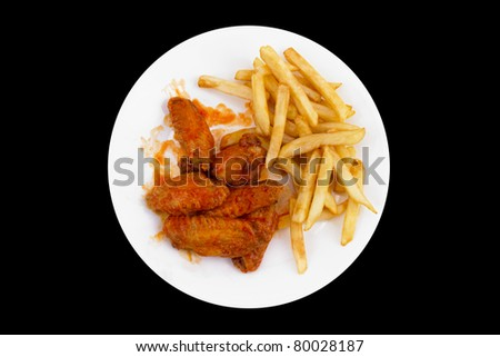 Plate of Buffalo Chicken Wings and Fries Isolated on a Black Background.  This file includes a clipping path.