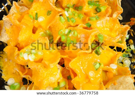 Plate of cheese nachos topped with thin sliced green onion