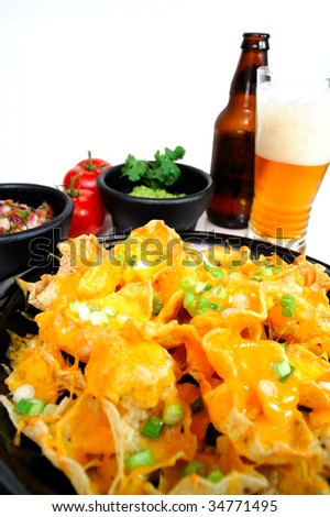 Plate of cheese nachos with sides of guacamole and salsa with an ice cold bottled beer poured in a glass