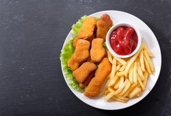 plate of chicken nuggets with french fries on dark background, top view