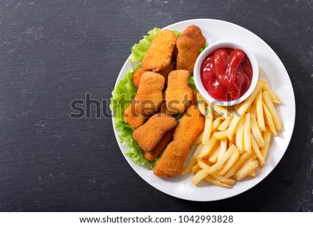 plate of chicken nuggets with french fries on dark background, top view Сток-фото ©