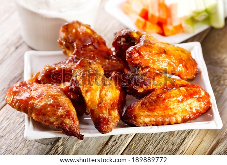 plate of chicken wings on wooden table