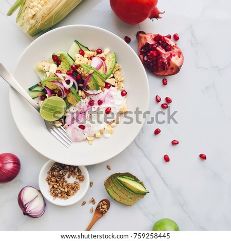 Plate of colorful healthy salad with avocado, sweet corn, pomegranate, cucumber, red onion, lime, greek yogurt and sunflower seeds on a marble background, top view