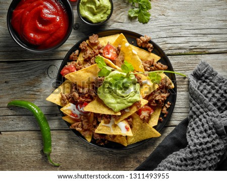 plate of corn chips nachos with fried minced meat and guacamole on wooden kitchen table, top view Foto stock ©