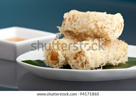 Plate of crispy taro root crusted Thai spring rolls appetizer with sweet and savory dipping sauce.
