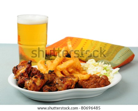 Plate of delicious barbecued chicken wings with beer.