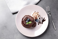 Plate of delicious fresh fondant with hot chocolate and blueberries on table, top view. Lava cake recipe