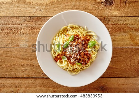 Plate of delicious spaghetti Bolognaise or Bolognese with savory minced beef and tomato sauce garnished with parmesan cheese and basil, overhead view #483833953