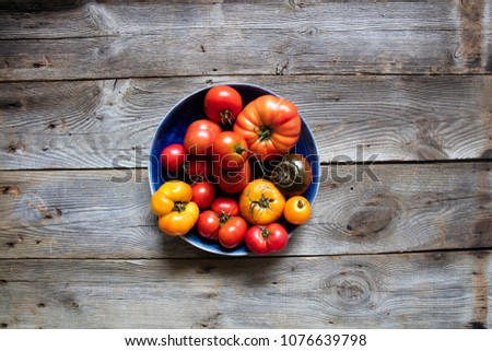 plate of different heirloom colorful tomatoes on beautiful old wooden table for genuine organic mediterranean diet and earthy gardening, copy space, top view