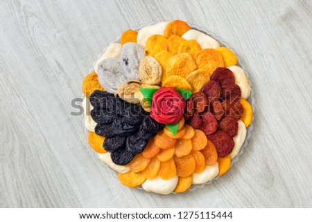Plate of dried fruits on white wooden background. Decorative plate isolated. Oriental sweets: Plum, dried apricot, dried Apple, candy. Vegetarian food. A raw food diet