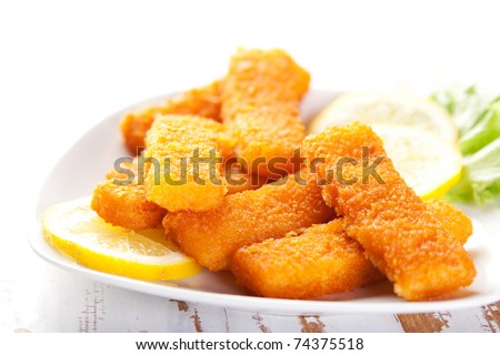 Plate of fish fingers with lemon and salad