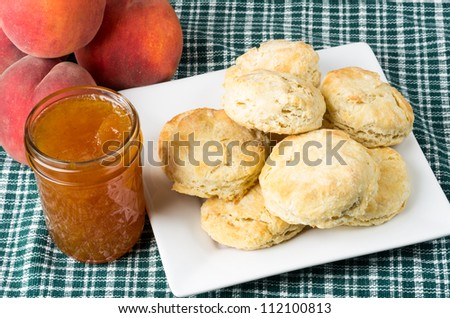 Plate of fresh biscuits or scones with peach jelly