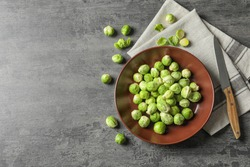 Plate of fresh Brussels sprouts, napkin and knife on grey background, top view with space for text