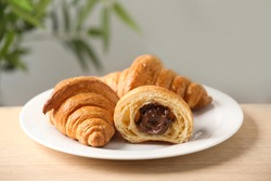 Plate of fresh croissants with chocolate stuffing on wooden table indoors, closeup. French pastry