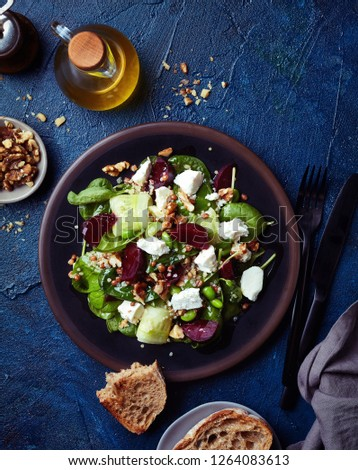 Plate of fresh healthy vegetable and quinoa salad with spinach, cucumber, beet and feta cheese on blue background. Top view