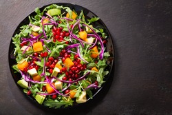 plate of fresh salad with rucola, pomegranate seeds, avocado, pumpkin and purple cabbage on dark background, top view