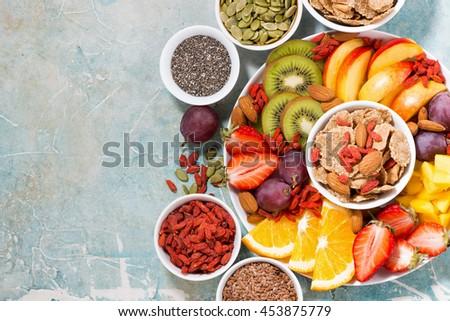 plate of fresh seasonal fruits and superfoods and rustic background, top view, horizontal #453875779