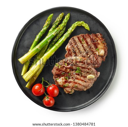 plate of freshly grilled juicy beef steak meat with thyme and asparagus isolated on white background, top view