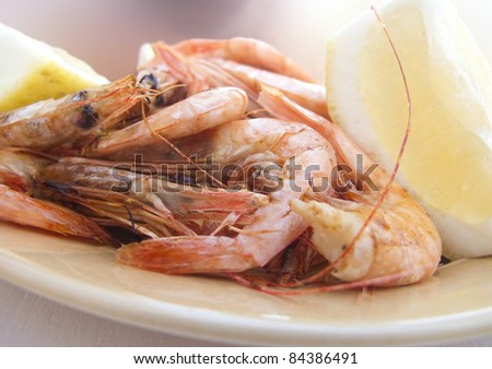 Plate of freshly grilled shrimp in the shell, with lemon wedges