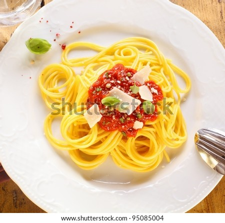Plate of freshly prepared spaghetti bolognaise with a tomato sauce and cheese ready to be served.
