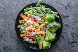 Plate of frozen vegetables on a gray table. Concept of saving time on cooking dinner and convenient storage of ready made frozen dishes.