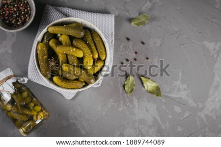 Plate of gherkins, pickled cucumbers on a grey concrete background. Clean eating, vegetarian food concept. Top view with space for text Photo stock ©