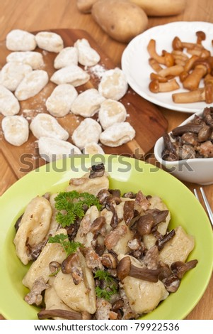 Plate of Gnocchi with Sausage and Wild Mushrooms Sauce and Ingredients on a Table