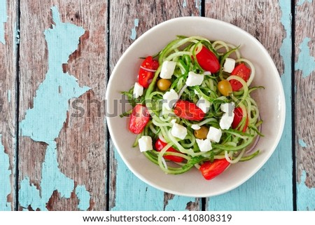 Plate of Greek Salad with cucumber noodles, overhead view on rustic wood background #410808319