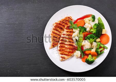 plate of grilled chicken with vegetables on dark background, top view