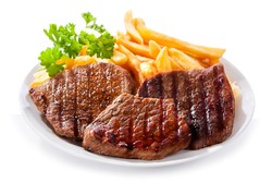 plate of grilled meat with fries on white background