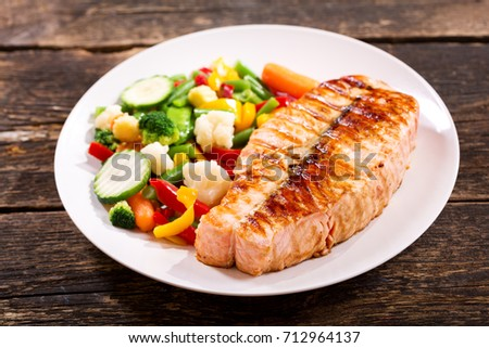 plate of grilled salmon steak with vegetables on wooden table