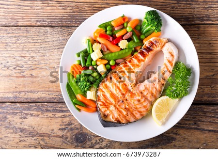 plate of grilled salmon steak with vegetables on wooden table, top view #673973287