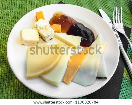 Plate of сheese ыlices and jam. Studio Photo
