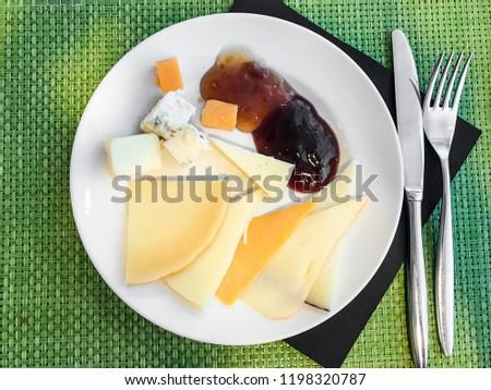 Plate of сheese ыlices and jam. Studio Photo