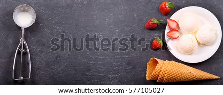 plate of ice cream scoops with fresh strawberry and waffle cones on dark background, top view with copy space