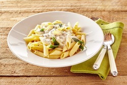 Plate of Italian penne pasta topped with a creamy sauce with basil and seasoning served on a rustic wooden table with utensils and napkin
