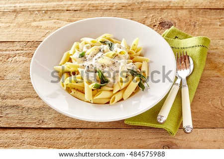 Plate of Italian Penne pasta topped with a formaggio creamy savory sauce and basil served in a white dish on a rustic wood table