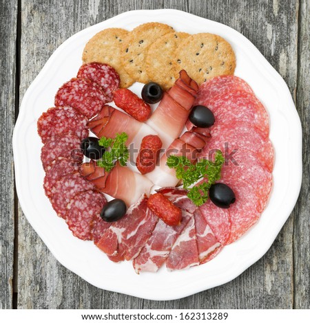plate of meat delicacies and crackers, top view, close-up